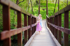 Two adorable little sisters having fun on a hanging bridge Royalty Free Stock Image