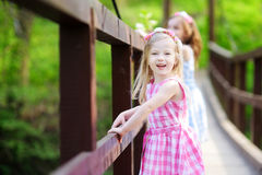 Two adorable little sisters having fun on a hanging bridge Stock Photography