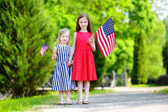 Two adorable little sisters holding american flags outdoors on beautiful summer day Royalty Free Stock Photography