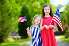 Two adorable little sisters holding american flags outdoors on beautiful summer day Stock Image