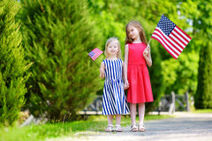 Two adorable little sisters holding american flags outdoors on beautiful summer day Stock Photography