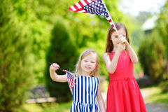Two adorable little sisters holding american flags outdoors on beautiful summer day. Royalty Free Stock Photos