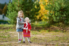 Two adorable little sisters holding the big TWO Royalty Free Stock Photography