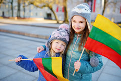Two adorable little sisters holding Lithuanian flags in Vilnius Stock Photo