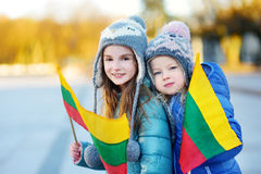 Two adorable little sisters holding Lithuanian flags in Vilnius Royalty Free Stock Image