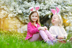 Two adorable little sisters hunting for easter egg in blooming spring garden Royalty Free Stock Photography