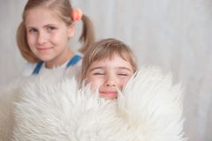 Two adorable little sisters laughing and hugging each other.  Stock Photos
