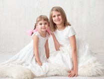 Two adorable little sisters laughing and hugging each other. In studio. Great sister`s love Stock Photography