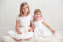 Two adorable little sisters laughing and hugging each other. In studio. Great sister& x27;s love Stock Images