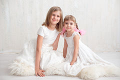 Two adorable little sisters laughing and hugging each other. In studio. Great sister& x27;s love Royalty Free Stock Images