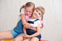 Two adorable little sisters laughing and hugging each other. In studio. Great sister& x27;s love Royalty Free Stock Photos