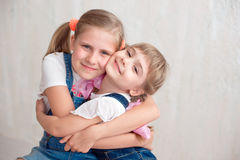 Two adorable little sisters laughing and hugging each other. In studio. Great sister& x27;s love Stock Photography
