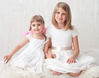 Two adorable little sisters laughing and hugging each other. In studio. Great sister`s love Royalty Free Stock Photography