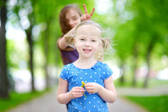 Two adorable little sisters laughing and hugging each other Stock Photography