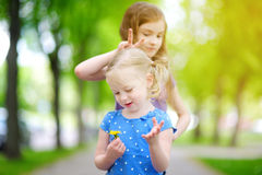 Two adorable little sisters laughing and hugging each other. On warm and sunny summer day Royalty Free Stock Images
