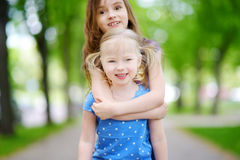 Two adorable little sisters laughing and hugging each other. On warm and sunny summer day Royalty Free Stock Photography