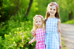 Two adorable little sisters laughing and hugging each other. On warm and sunny summer day Stock Photography