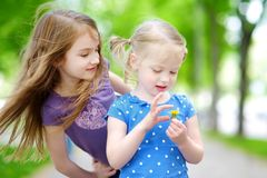 Two adorable little sisters laughing and hugging each other. On warm and sunny summer day Stock Photo
