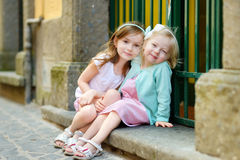 Two adorable little sisters laughing and hugging. Each other on warm and sunny summer day in italian town Stock Image