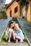 Two adorable little sisters laughing and hugging. Each other on warm and sunny summer day in italian town Royalty Free Stock Photos