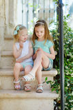 Two adorable little sisters laughing and hugging. Each other on warm and sunny summer day in italian town Royalty Free Stock Photography