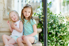 Two adorable little sisters laughing and hugging. Each other on warm and sunny summer day in italian town Stock Photo