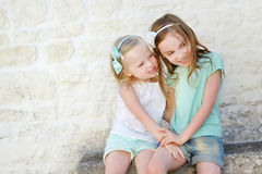 Two adorable little sisters laughing and hugging. Each other on warm and sunny summer day in italian town Royalty Free Stock Photo