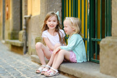 Two adorable little sisters laughing and hugging each other on warm and sunny summer day. In italian town Royalty Free Stock Image