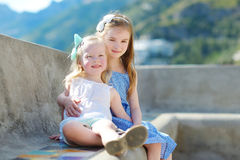 Two adorable little sisters laughing and hugging each other on warm and sunny summer day. In italian town Royalty Free Stock Photo