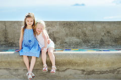 Two adorable little sisters laughing and hugging each other on warm and sunny summer day. In italian town Stock Photo