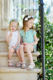 Two adorable little sisters laughing and hugging each other. On warm and sunny summer day in italian town Stock Images