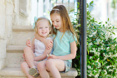 Two adorable little sisters laughing and hugging each other. On warm and sunny summer day in italian town Stock Image
