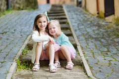 Two adorable little sisters laughing and hugging each other on warm and sunny summer day. In italian town Stock Image
