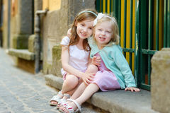 Two adorable little sisters laughing and hugging each other on warm and sunny summer day. In italian town Royalty Free Stock Images