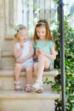 Two adorable little sisters laughing and hugging each other. On warm and sunny summer day in italian town Royalty Free Stock Photography