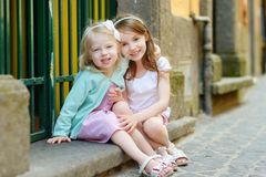 Two adorable little sisters laughing and hugging each other on warm and sunny summer day. In italian town Royalty Free Stock Photography
