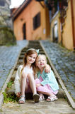 Two adorable little sisters laughing and hugging each other on warm and sunny summer day. In italian town Royalty Free Stock Photos