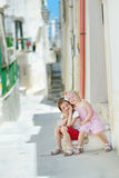 Two adorable little sisters laughing and hugging. Each other on warm and sunny summer day in Vieste, Italy Stock Image