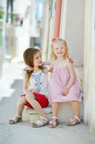 Two adorable little sisters laughing and hugging. Each other on warm and sunny summer day in Vieste, Italy Stock Photo