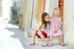 Two adorable little sisters laughing and hugging. Each other on warm and sunny summer day in Vieste, Italy Royalty Free Stock Image