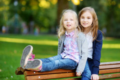 Two adorable little sisters laughing and hugging on summer day in a park Royalty Free Stock Photos