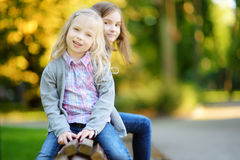 Two adorable little sisters laughing and hugging on summer day in a park Royalty Free Stock Photography