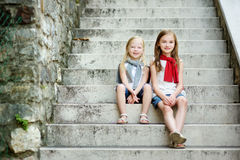 Two adorable little sisters laughing and hugging on warm and sunny summer day Stock Images