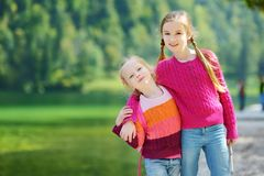 Two adorable little sisters laughing and hugging on warm and sunny summer day near Konigssee lake, Germany Royalty Free Stock Photo