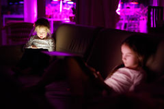 Two adorable little sisters playing with a digital tablet in a dark room royalty free stock images