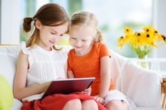 Two adorable little sisters playing with a digital tablet Royalty Free Stock Images