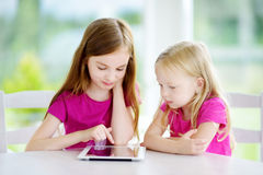 Two adorable little sisters playing with a digital tablet stock photos