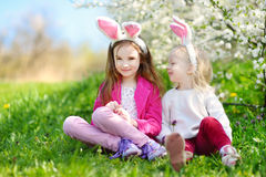 Two adorable little sisters playing with Easter eggs on Easter day Royalty Free Stock Photos