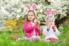 Two adorable little sisters playing with Easter eggs on Easter day Stock Photos