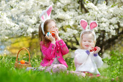 Two adorable little sisters playing with Easter eggs on Easter day Royalty Free Stock Images